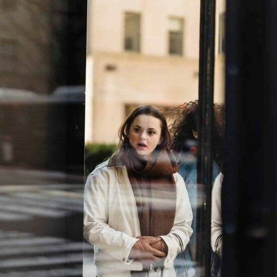 Amazed woman standing near glass showcase of store