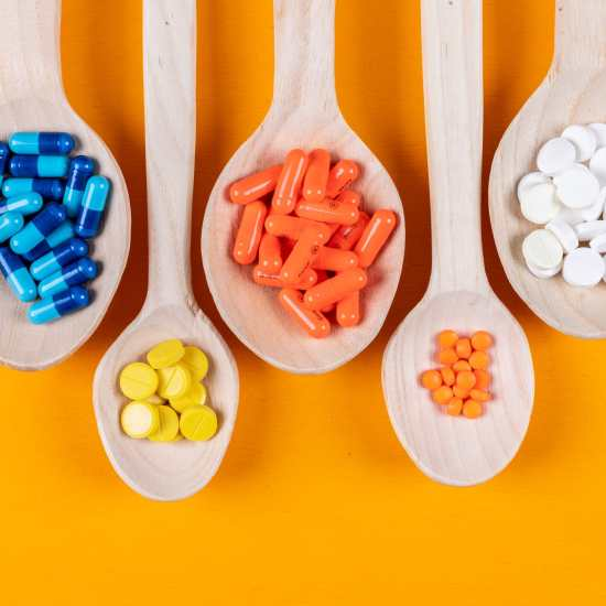 Top view colorful pills in wooden spoons on orange background. horizontal