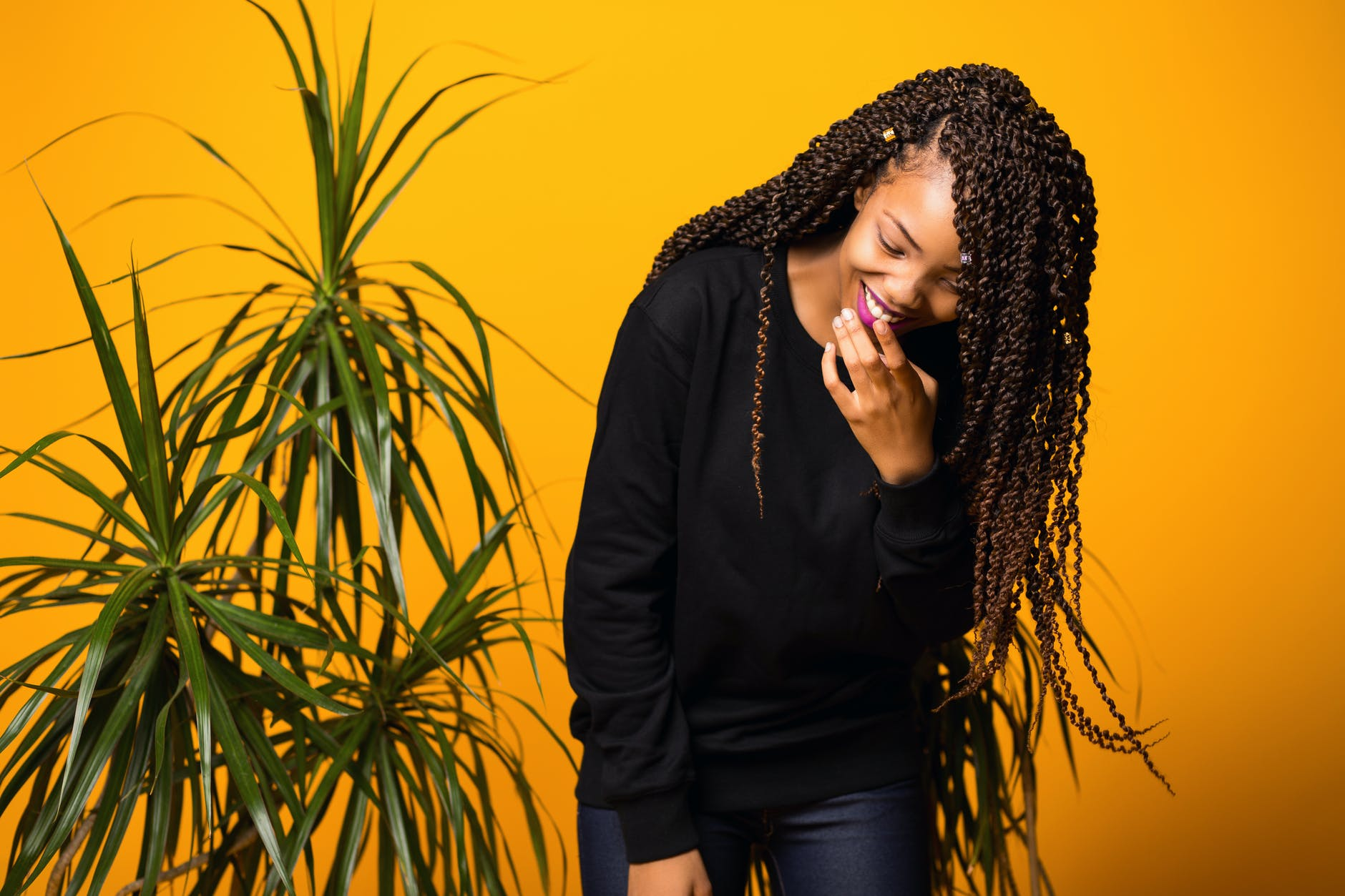 optimistic young black female having fun in yellow studio