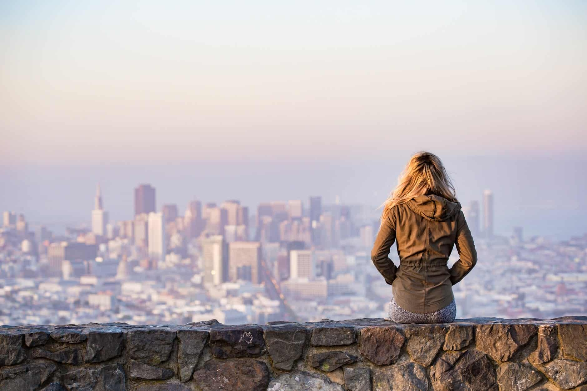 woman on rock platform viewing city, showing financial freedom