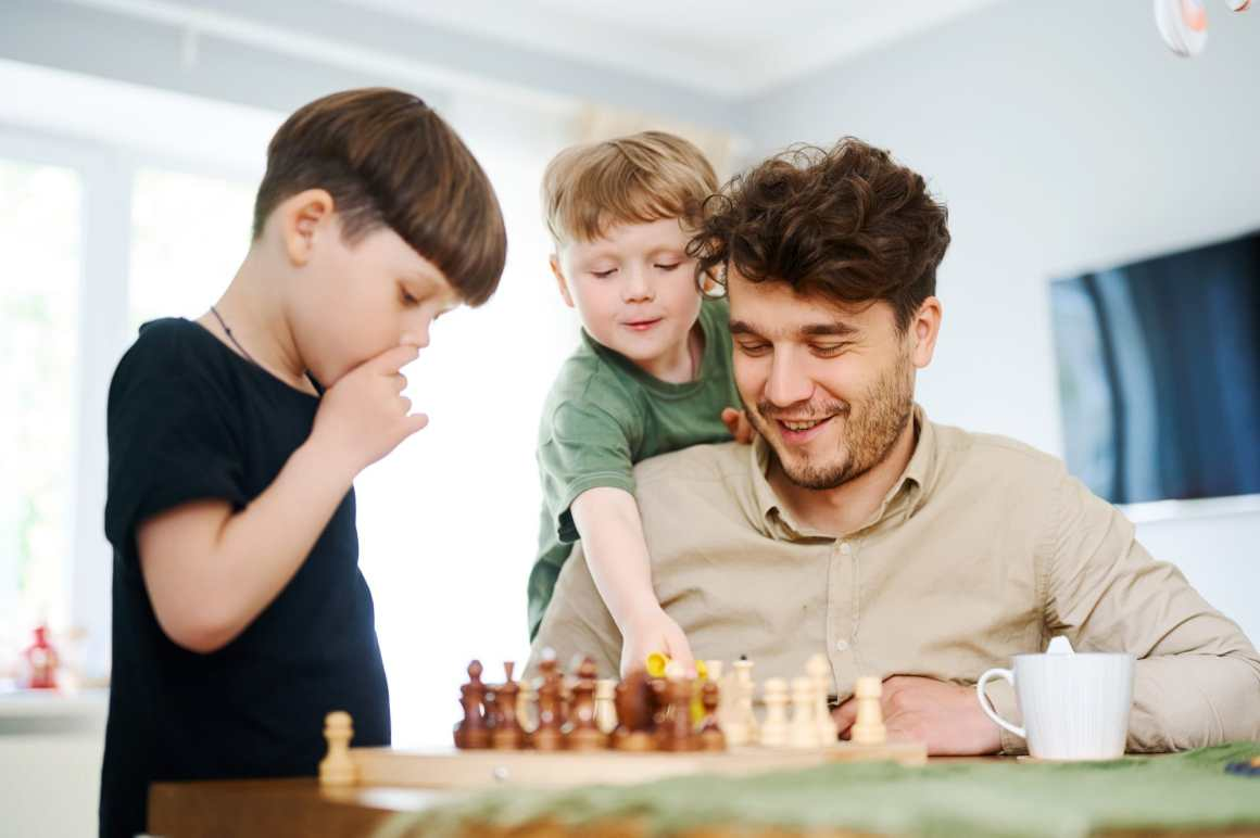 father teaching sons how play chess - best chess books for beginners