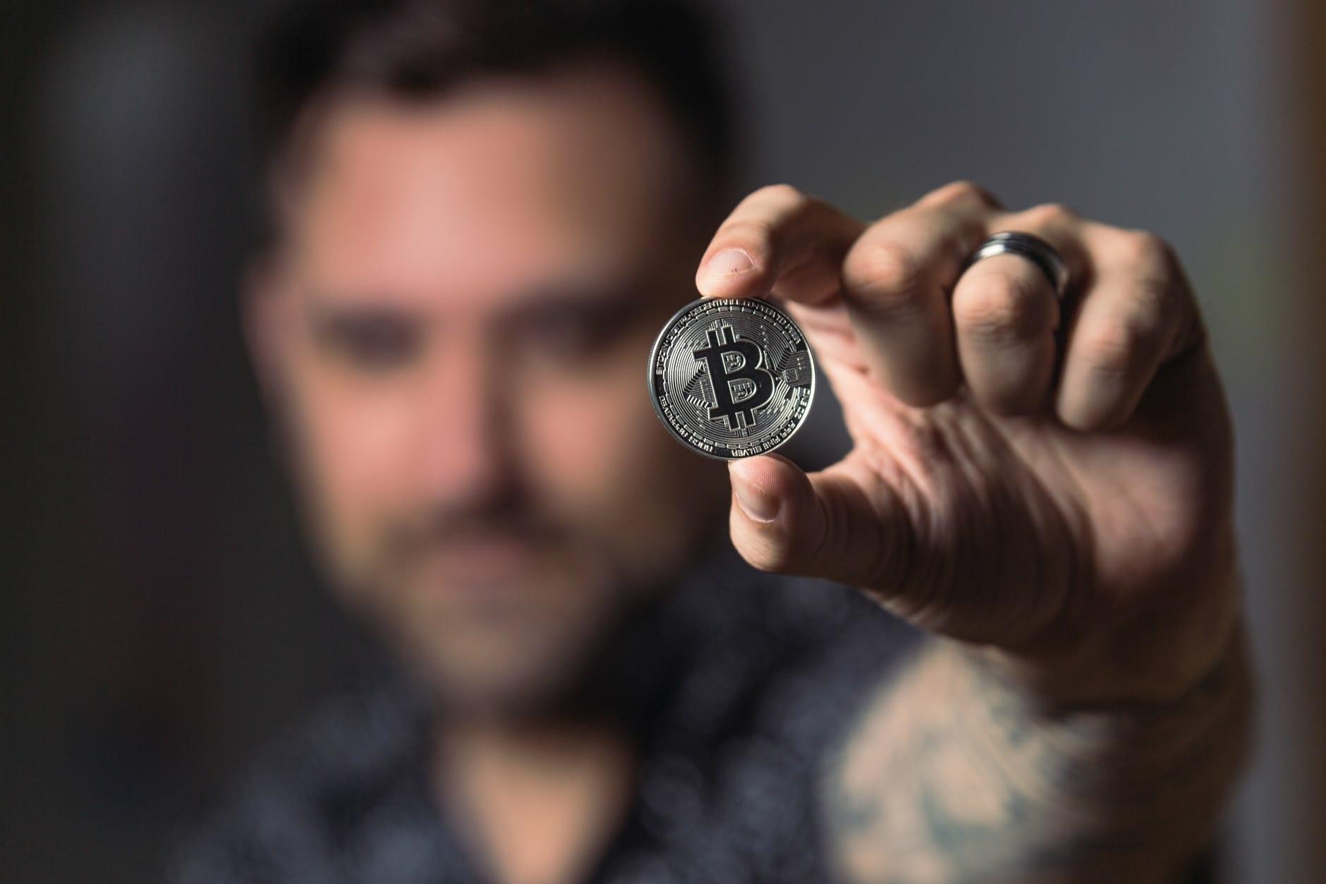 Person holding silver bitcoin coin