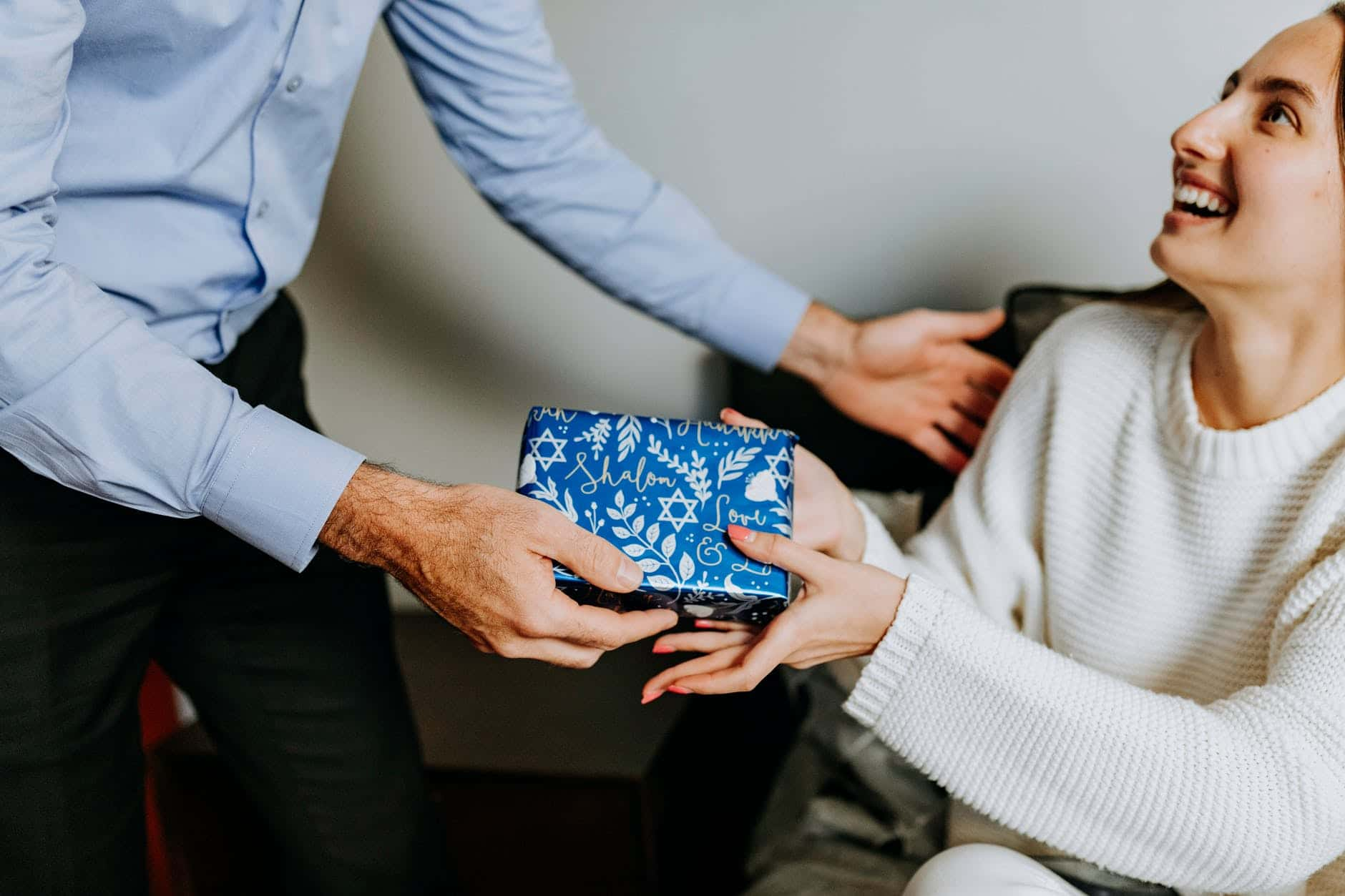 Photo of person handing gift to woman to showcase the best gifts for college students in canada